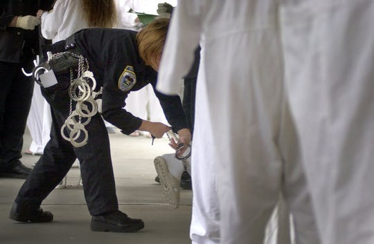 A corrections officer puts ankle cuffs on inmates at Oregon Women's Correctional Center as they get ready to load a bus to their new home at the Coffee Creek Correctional Facility in Wilsonville on Apr. 26, 2004.