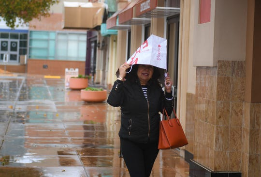 Alicia Calderon uses a Macy's paper bag to shield herself from the rain on Jan. 16, 2020.