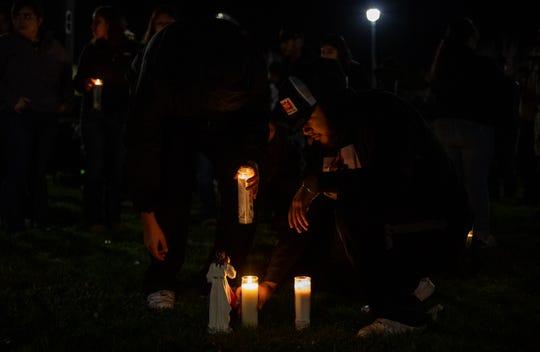 Steven Vargas, 17, sets a candle on the grass during Adrianna Annalie Vergara Juarez's vigil on Jan. 15, 2020.
