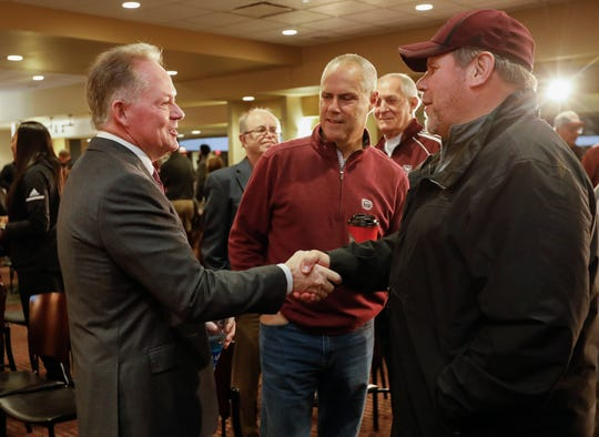 New Missouri State University Head Football Coach Bobby Petrino, left, shakes hands with Scott Opfer, right, and Scott Bailes, center, after a press conference at JQH Arena on Thursday, Jan. 16, 2020.
