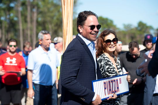Former New York Mets catcher Mike Piazza and his wife, Alicia Piazza, pose for photos under a newly unveiled sign revealing Piazza Drive on Thursday, Jan. 16, 2020, at Clover Park in Port St. Lucie.