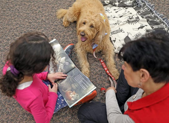 Michaela Dworkin, 8 reads to Meeka and her handler Lorraine Brown at Pearl River Library on Jan. 15, 2020.