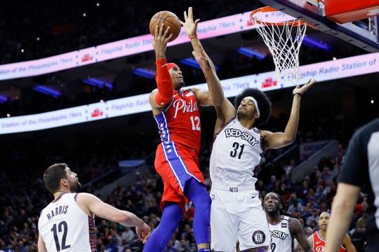 Philadelphia 76ers' Tobias Harris, left, goes up for a shot against Brooklyn Nets' Jarrett Allen during the first half of an NBA basketball game, Wednesday, Jan. 15, 2020, in Philadelphia. (AP Photo/Matt Slocum)