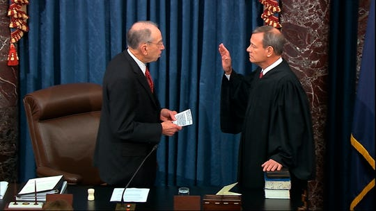 Chief Justice John Roberts, right, placed his hand on the Bible and took an oath before presiding over the Senate impeachment trial of President Donald Trump in January. Now he is at the center of several religious freedom cases at the Supreme Court.