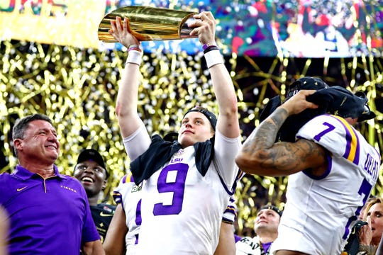 LSU Tigers head coach Ed Orgeron and LSU Tigers quarterback Joe Burrow (9) celebrate with the National Championship trophy after beating Clemson Tigers in the College Football Playoff national championship game at Mercedes-Benz Superdome.