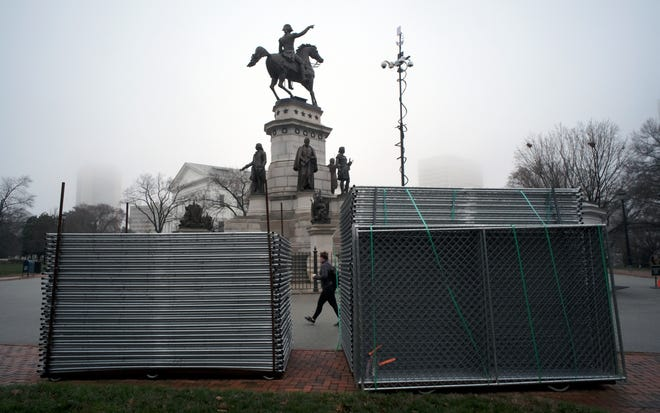 Stacks of chain-link fencing and a tower with security cameras beside the equestrian statue of George Washington outside the State Capitol in Richmond, Va., Tuesday, Jan. 14, 2020.