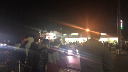 """Spectators line Ocean Avenue at 8th Avenue in front of the 7-Eleven, for what police called a """"Pop Up Car Meet"""" on the evening of Saturday, Jan. 11, 2020."""