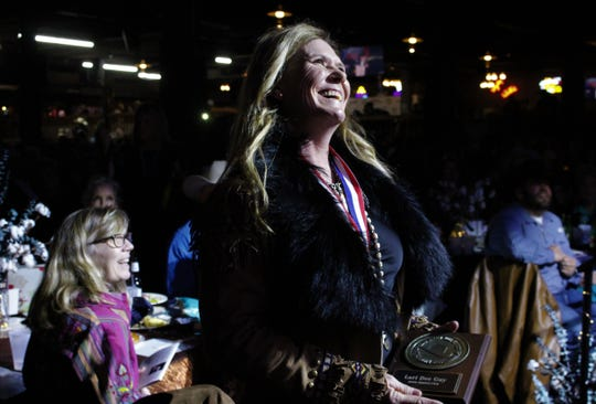 Lari Dee Guy laughs at a story told by mistress of ceremonies Pam Minick, about the time Minick outperformed Guy at a rodeo event. Guy had just received her medal and plaque as a 2020 inductee into the Texas Cowboy Hall of Fame on Thursday at Billy Bob's Texas in Fort Worth.