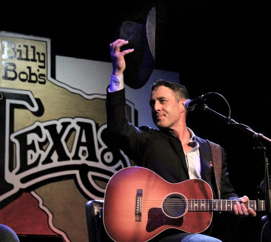 Country singer Aaron Watson tips his cowboy hat to the crowd in thanks for honoring his induction Thursday to the Texas Cowboy Hall of Fame at Billy Bob's Texas in Fort Worth. Watson had just played for the 800 or so in the audience.