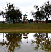 Playground equipment is reflected in a large puddle at C.W. Gill Park in Abilene Friday, the result of overnight and morning rainfall.