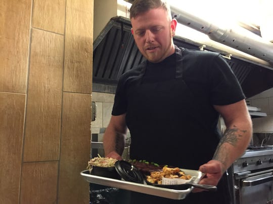 Shawn Careau holds a tray of baby-back ribs, roasted cauliflower and coleslaw in the kitchen of Smokey's Pit Stop inside Orlando's Bar in Burlington on Jan. 16, 2020.