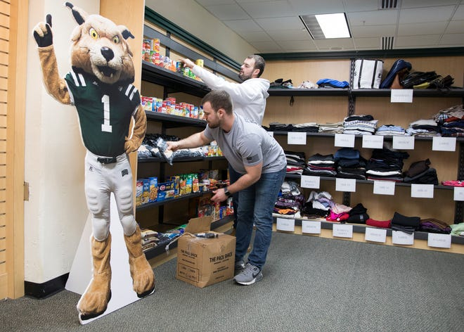 Cody Anderson and Matt Bush work on stocking the shelves of the food pantry at Ohio University-Chillicothe. The pantry is made up shelves filled with not only clothing, but non-perishable items like canned fruit, instant waffles, oatmeal, and rice.