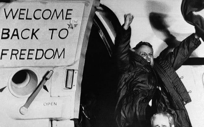 """Freed U.S. hostage David Roeder shouts and waves as he arrives at Rhein-Main U.S. Air Force base in Frankfurt, West Germany from Algeria on January 21, 1981.  He was among 52 Americans held hostage in Iran for 444 days after their capture at the U.S. Embassy in Tehran. The sign on the airplane door reads, """"Welcome back to Freedom."""""""