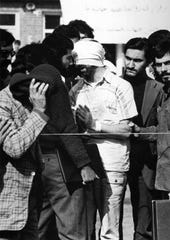 One of the U.S. hostages held in Iran, blindfolded and with his hands bound, is displayed to the crowd outside the U.S. Embassy in Tehran.