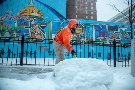 Cody Cariaga of Des Moines shovels snow off the sidewalk on Fourth Street. in Des Moines Friday, Jan. 17, 2020.