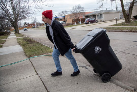 Mike Schutter, 28, rolls his garbage can back up to his house Friday, Jan. 17, 2020 across the street from his neighbor (PT Cruiser in driveway) Patricia Bennett who was allegedly murdered by her 50-year-old daughter in their Roseville home.