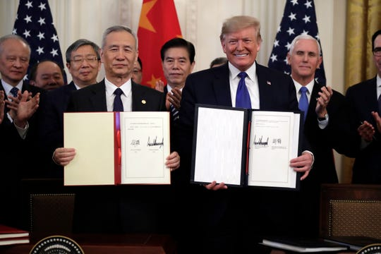 In this Wednesday, Jan. 15, 2020, file photo, U.S. President Donald Trump, right, signs a trade agreement with Chinese Vice Premier Liu He, in the East Room of the White House, in Washington.