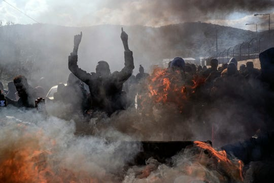 FILE - Refugees and migrants burn garbage bins and chant slogans as they demonstate outside Moria camp, following the stabbing death of an 20-year-old man from Yemen in the Greek island of Lesbos, Friday, Jan, 17, 2020.