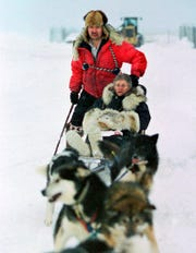 In this Jan. 19, 2000, file photo, U.S. Census Bureau director Kenneth Prewitt, seated, gets a dog sled ride into town by Harold Johnson after arriving for the first count in the Eskimo village of Unalakleet, Alaska.