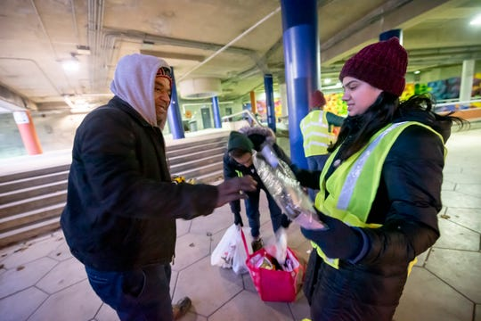 Medical student Riya Malhotra, right, a volunteer with Detroit Street Care, gives out blankets and other cold weather essentials to a man named James near Hart Plaza, in Detroit, January 16, 2020.  Detroit Street Care gives assistance and medical care to homeless people in Detroit.