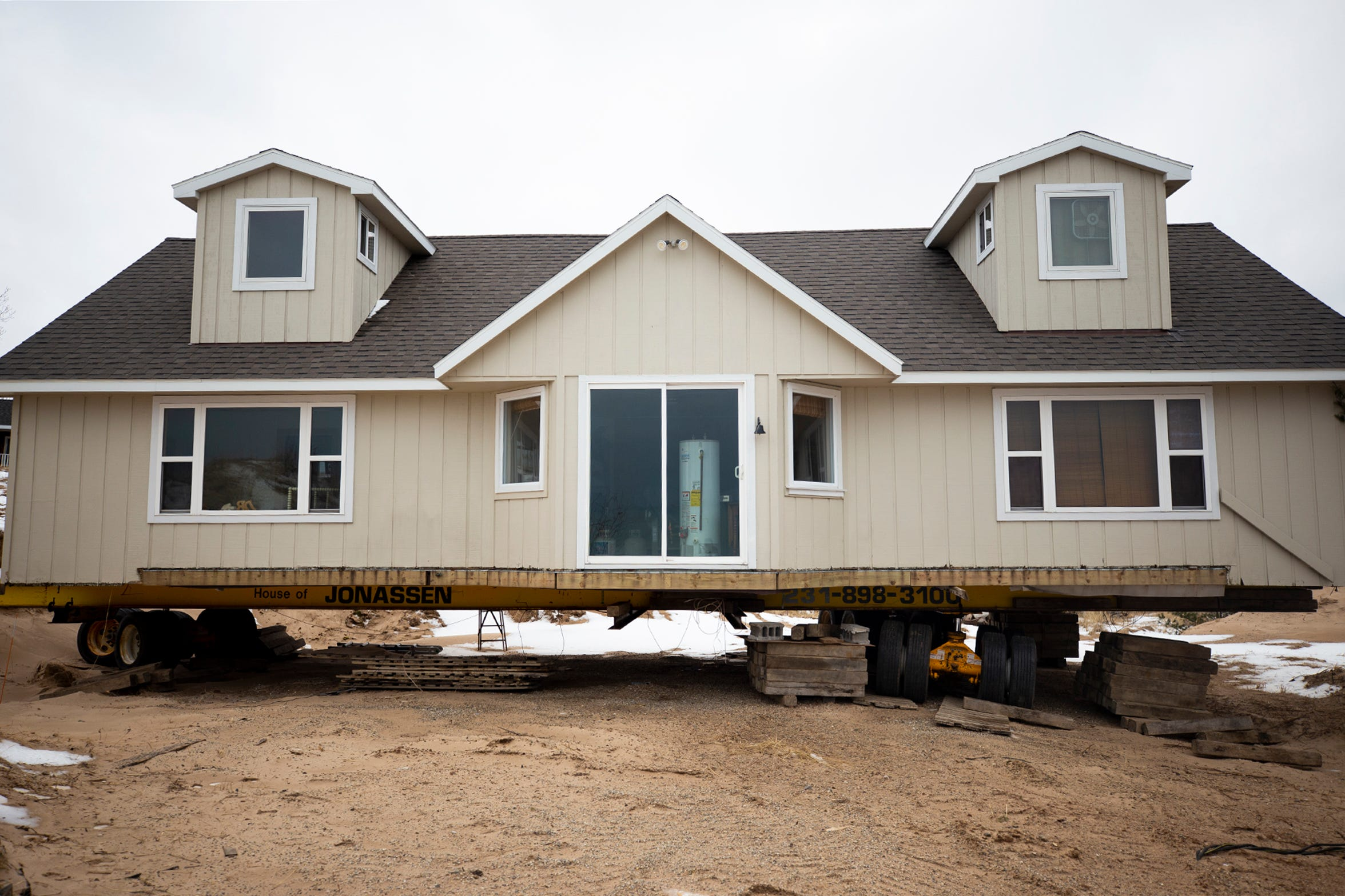 A house remains lifted after being moved back from the edge of the bluffs overlooking Lake Michigan on what once was North Lakeshore Drive at Juniper Beach in Golden Township. Part of North Lakeshore Drive has fallen into Lake Michigan due to high lake levels causing shoreline erosion.
