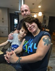 """Nic Cohoon, 10, who has neurofibromatosis, with mother Sheila Cohoon, with her """"End NF"""" arm tattoo, and dad Daryl Cohoon in their kitchen in Clinton Township home."""