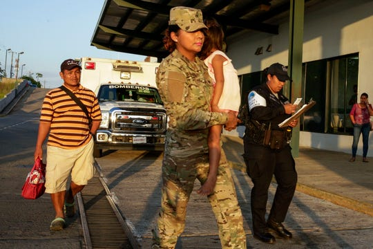 Jose Gonzalez, left, follows his 5-year-old daughter, carried by a police officer, as they leave a hospital in Santiago, Panama, Thursday, Jan. 16, 2020.
