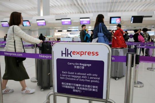 Passengers wait at the check-in counter of Hong Kong Express Airways at Hong Kong International Airport.