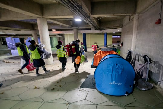 Volunteers with Detroit Street Care walk through a homeless camp in Hart Plaza in Detroit, January 16, 2020.  The organization, made up of medical students from Michigan State University's College of Osteopathic Medicine, gives medical care and other assistance to the homeless population in the city.