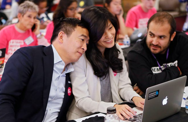 FILE- In this Nov. 21, 2019, file photo, Democratic presidential candidate former technology executive Andrew Yang, leans on his wife with his wife Evelyn, as they join in at a Fair Fight phone bank at Ebenezer Baptist Church in Atlanta.