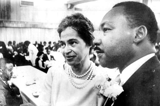 The Rev. Martin Luther King Jr. stands beside Rosa Parks at a dinner given in her honor in Birmingham, Ala. in 1965.