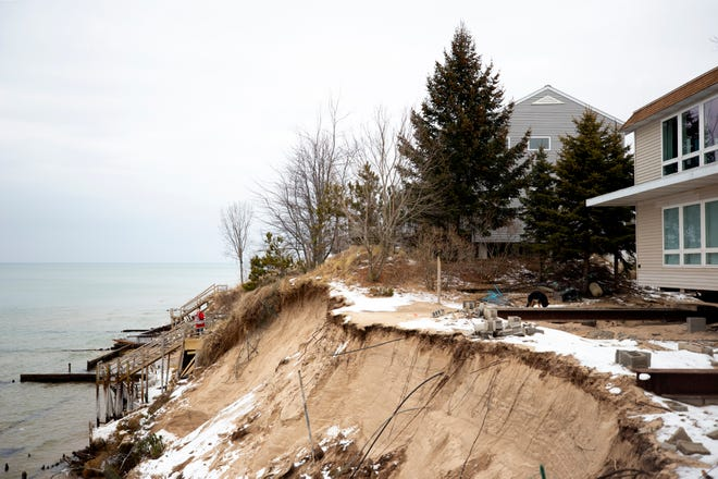 Norma Mendenhall (red coat), 88, takes a photo of her home as she stands on a staircase leading down to Lake Michigan in Shelby, south of Ludington. Norma has lived here for 58 years but now bluff erosion threatens to destroy her home and those of her neighbors.