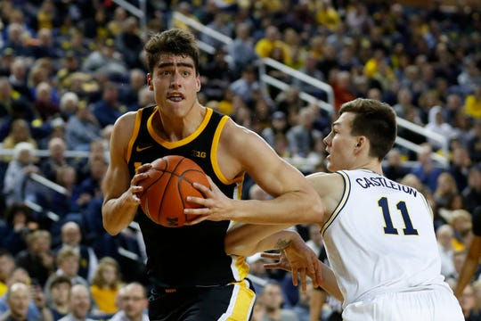 Iowa's Luka Garza drives on Michigan's Colin Castleton during the first meeting between the teams in December.