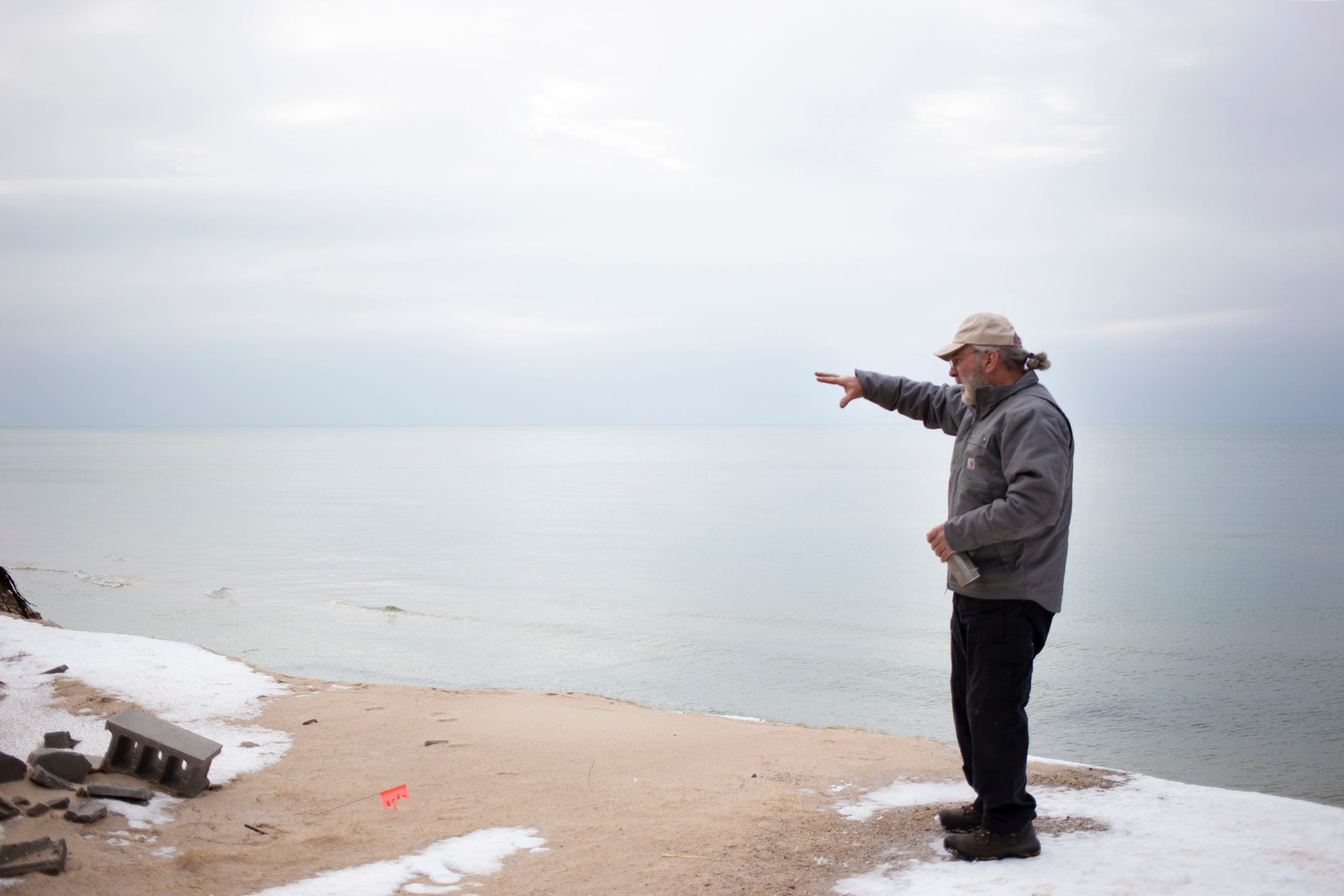 Phil Jonassen of Jonassen Inc. Structural Movers points out the erosion that has taken place since he started working to move houses in Shelby, Mich. threatened by the erosion of the Lake Michigan shoreline.