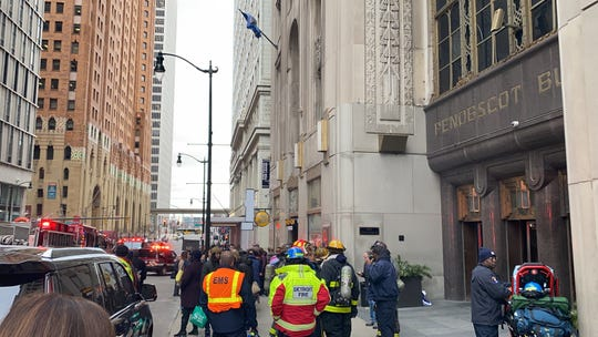 Fire and EMS officials clear the sidewalk out front of the Griswold entrance of the Penobscot Building in Detroit.