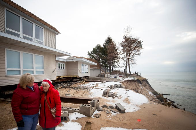 Dawn Mendenhall embraces her mother Norma Mendenhall after looking at the erosion that high lake levels have caused on her property on the Lake Michigan shoreline in Shelby, Mich. Norma Mendenhall has lived in the home for 58 years. The home has been moved back from the edge of the bluff to protect it from sliding into the lake.
