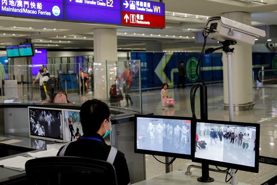 FILE - In this Jan. 4, 2020, file photo, a health surveillance officer monitors passengers arriving at the Hong Kong International airport in Hong Kong.