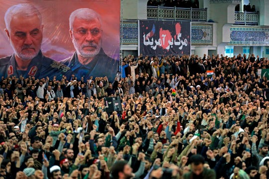 In this picture released by the official website of the office of the Iranian supreme leader, worshippers chant slogans during Friday prayers ceremony, as a banner show Iranian Revolutionary Guard Gen. Qassem Soleimani, left, and Iraqi Shiite senior militia commander Abu Mahdi al-Muhandis, who were killed in Iraq in a U.S. drone attack on Jan. 3.