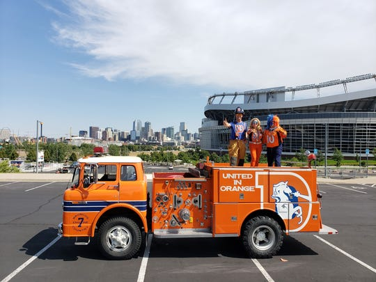 Broncos' super fan Robert Garner stands on top of his orange No. 7 firetruck in the parking lot at Empower Field at Mile High with his pregame tailgate partners.
