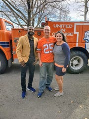 Robert Garner, center, a Denver Broncos super fan and finalist for the NFL's Ford Hall of Fans, is pictured in front of his orange No. 7 fire engine with Pro Football Hall of Famer Champ Bailey and Garner's wife, Emily, outside their Fort Collins home.