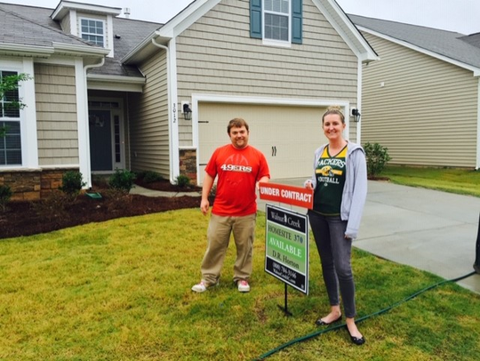 San Francisco 49ers fan Josh Jeanes and wife Jessica, in Packers gear, pose outside their house in Lancaster, S.C.
