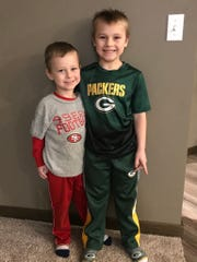 Blake, left, and Colin Rebman have begun to pay attention to pro football. Their father, Travis, hopes they'll become fans of his beloved 49ers, but mom Amanda would prefer that they'll cheer for her Green Bay Packers.