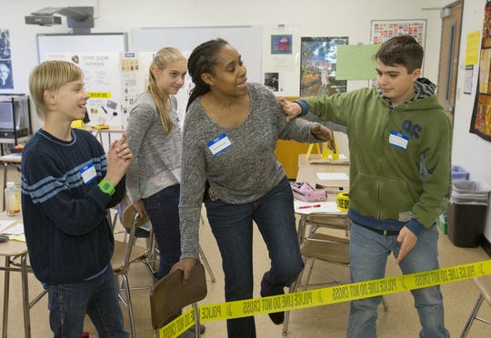 DeWitt Middle School students watch as Ithaca City Police Officer Christine Barksdale, playing the victim of a break in, is kept from the scene by a student during a lesson about evidence gathering and police procedures during DeWitt Middle School's annual career day in December 2014.