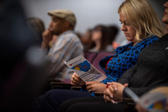 A woman reads a pamphlet about navigating the opioid crisis as an employer at a Tennessee Chamber of Commerce presentation at Ayers Auditorium in Jackson, Tenn., on Friday, Jan. 17, 2020.
