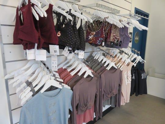 Yoga clothes for sale hang on the racks at the Yoga Six studio on Jan. 13, 2020.