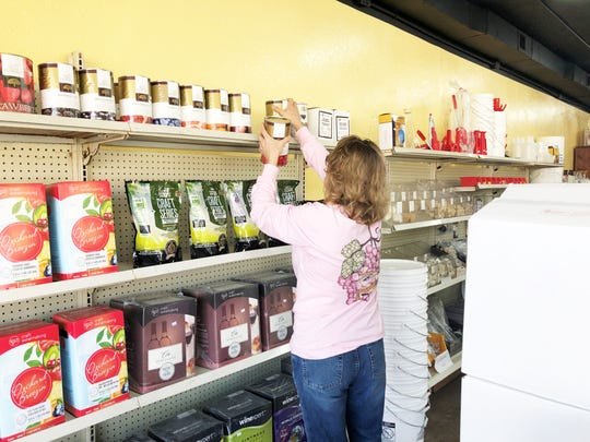 Allen Biermakens owner Deanna Pierce stocks the shelves with wine making supplies at her new Chapman Highway location on Jan. 16, 2020.