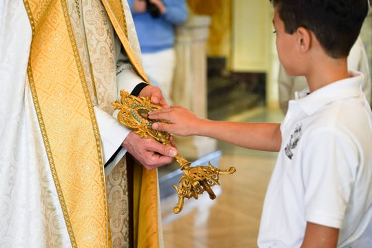 Father Andrew Schumacher, parochial vicar for the Cathedral of St. John the Evangelist, holds relics of Saint Mary Magdalene as Cathedral-Carmel School students and faculty approach for Veneration.