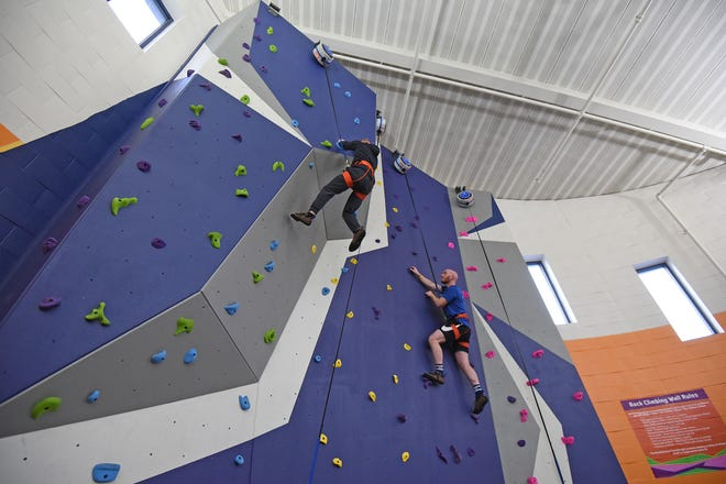 Kyle Proulx and Ryan Freehafer, both YMCA employees, scale the new 24-foot rock climbing wall at the Mansfield Area Y after the ribbon-cutting ceremony Thursday afternoon.