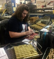 Amy Caldwell, assembly associate, carefully inserts high tolerance components into a padlock's internal mechanism.