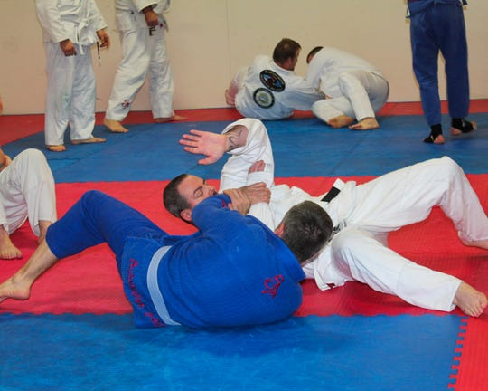 Mike Dalton, a blue belt in Gracie jiu-jitsu under Shawn Chitwood, trains with local resident Tom Ballard during Monday night's class at Marion Fitness Club, 1295 Harding Hwy E., Sara Ave. entrance. Since October, Team Chitwood Martial Arts and Fitness has been offering jiu-jitsu classes at 7 p.m. Mondays and Wednesdays and 10 a.m. Saturdays. The grand opening is 7 p.m. Wednesday at The Club.